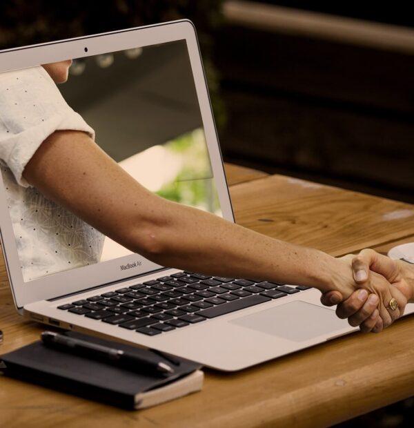 יד שיוצאת מהמסך מחשב לוחצת יד של אדם
